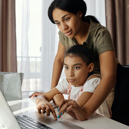 Woman teaching little girl how to use computer in their home